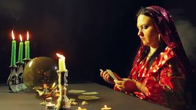 A young gypsy in a fortune-telling saloon by candlelight lays out cards for divination on the table. The average plan stock video footage