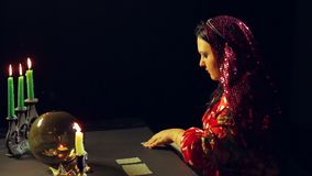 A young gypsy in a fortune-telling saloon by candlelight lays out cards for divination on the table. The average plan stock video