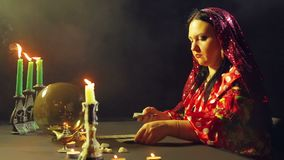 A young gypsy in a fortune-telling saloon by candlelight lays out cards for divination on the table. The average plan stock footage