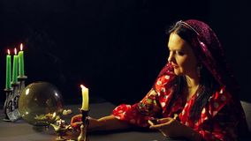 A young gypsy in a red dress at the divination table lights candles. The average plan. Side view stock video footage