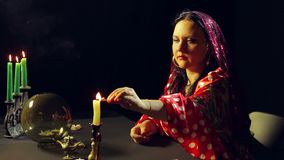 A young gypsy in a red dress at the divination table lights candles. The average plan. Side view stock footage