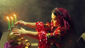 A young gypsy in a red dress at a table by candlelight reads the future on the ball. The average plan. Side view stock video footage