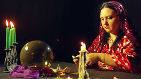 A young gypsy in a red dress at a table by candlelight reads the future with fortunetelling cards. The average plan. Side view stock video