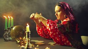 A young gypsy in a red dress at a table by candlelight reads the future on a magic ball. The average plan. Side view stock video footage