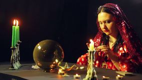 A young gypsy in a red dress at a table by candlelight reads the future over the stones. The average plan. Side view stock video footage