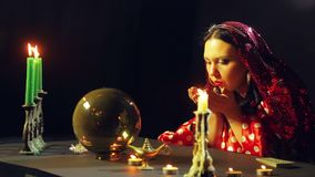 A young gypsy in a red dress at a table by candlelight reads the future over the stones. The average plan. Side view stock video