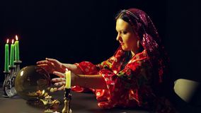 A young gypsy in a red dress at a table with candles looks into a glass ball and leads her hands over it. The average. Plan. Side view stock footage