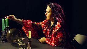 A young gypsy in a red dress at the table lights the candles. The average plan. Side view stock video