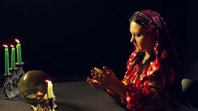 A young gypsy in a red dress at a table under candlelight throws pebbles at the table for divination. The average plan. Side view stock footage