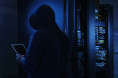 Young hacker in data security concept. Hooded computer hacker stealing information with Tablet PC, Server in the background Royalty Free Stock Photos
