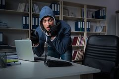 The young hacker hacking into computer at night. Young hacker hacking into computer at night Royalty Free Stock Photos