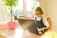 Young hacker little girl in glasses with a school backpack working at the computer, laptop.  royalty free stock photos