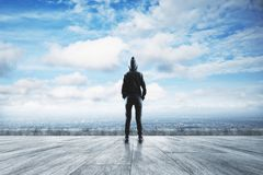 Criminal and research concept. Young hacker standing on concrete rooftop with city and sky view. Criminal and research concept royalty free stock photo