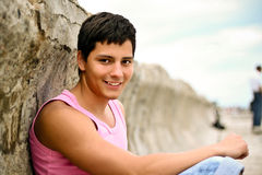 Young hadsome man. Glamour handsome teenager in pink t-shirt outdoors stock photography