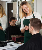Young hairdresser cutting hair of male teenager and smiling Royalty Free Stock Photo