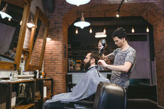Young hairdresser drying man's hair with blowdryer stock images