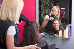 Young hairdresser makes hairstyle for beautiful girl Stock Photo
