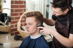 Young hairdresser trim hair to client in barber shop.  stock photos