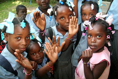 Young Haitian school girls and boys show friendship bracelets in village. Stock Images
