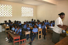 Young  Haitian school girls and boys with teacher in classroom. Royalty Free Stock Photography