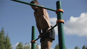 Young half-naked man spins on chinning bar outdoors. Workout on sports ground in summer. Athlete is pulling up on parallel bar. Blue sky on the background stock footage