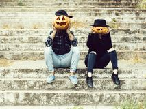 Halloween couple with pumpkin. Young halloween couple of men in cap and girl or women in black witch hat in jeans sitting on stony stairs with traditional autumn stock photos