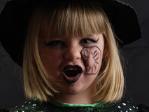 Young Halloween witch. Close up portrait of young girl dressed as Halloween witch, black background Royalty Free Stock Photos