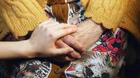 Young hand comforting a old pair of hands Royalty Free Stock Photo