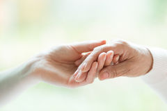 Young hand holding older one royalty free stock photography