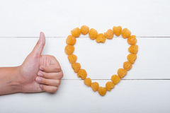 Young hand thumbs up. Like concept. Heart made raspberries Stock Photography