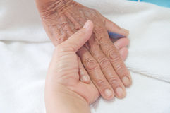 A young hand touches and holds. An old wrinkled hand Royalty Free Stock Photography
