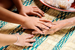 Young hand touches and holds an old woman hands Royalty Free Stock Photo