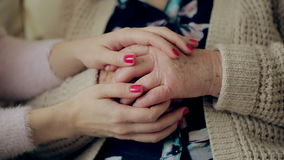 A young hand touches and holds an old wrinkled hand. Granddaughter holding a grandmother`s hand.