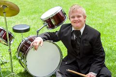 Young handicapped drummer next to drums. Royalty Free Stock Photos