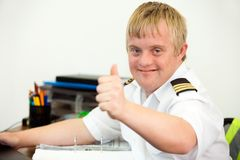 Young handicapped pilot showing thumbs up in office. Stock Photo