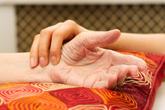 Young hands caring for old hands. On a red cushion Royalty Free Stock Photo