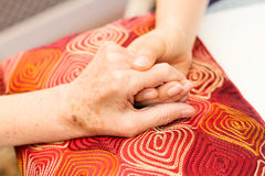 Young hands caring for old hands. On a red cushion Stock Photography