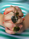 Young hands in prayer. A view of a young girls hands clasped in prayer with a necklace with a cross and hearts with the words peace, love and hope Royalty Free Stock Photography