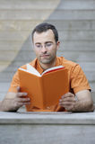 Young handsome adult reading a book Royalty Free Stock Photography