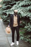 Young handsome african american businessman with hat walking in the city street royalty free stock photos