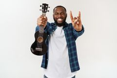 Young handsome african american man plays ukulele isolate over white background,. Young handsome african american man plays ukulele isolate over white background stock images