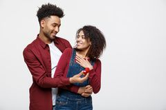 Young handsome african american man surprisingly ask her girlfriend for proposal. royalty free stock images