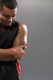 Young handsome African basketball player feeling. Feeling pain in elbow. Young muscular African man touching his elbow while standing against grey background Stock Photo