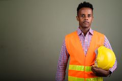 Young handsome African man construction worker against colored b stock image