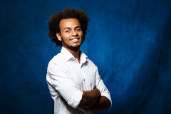Young handsome african man with crossed arms over blue background. Young handsome african man smiling, looking at camera, posing with crossed arms over blue Royalty Free Stock Photo