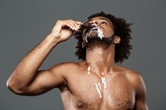 Young handsome african man eating icecream over grey background. Stock Photos