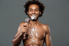 Young handsome african man eating icecream over grey background. Royalty Free Stock Photo