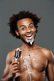 Young handsome african man eating icecream over grey background. Royalty Free Stock Photos