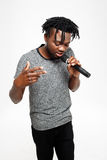 Young handsome african man singing in microphone over white background. Stock Image