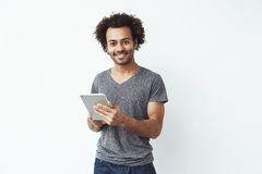 Young handsome african man smiling looking at camera holding silver tablet and playing games or using a booking app. Against white wall. Copy space Royalty Free Stock Images